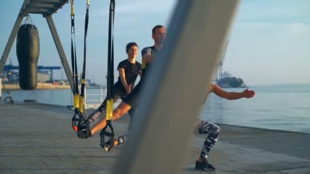 Sportovně založení lidé trénink dřepů s trx moře při východu slunce. Zpomalený pohyb