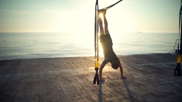 Silhouette of sportive man training with trx on floor at sunrise. Slow motion.