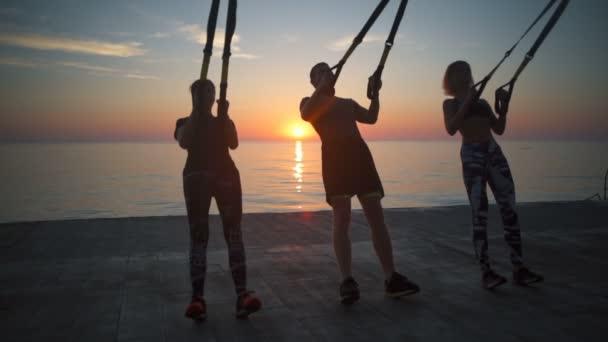 3 persone facendo esercizi con trx allalba. Slow motion.