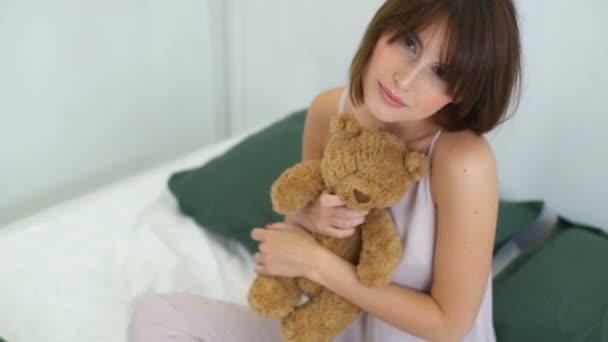 ženská modelka s medvědem v posteli pomalý pohyb