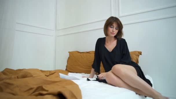 attractive woman in silk home dress sitting in bed