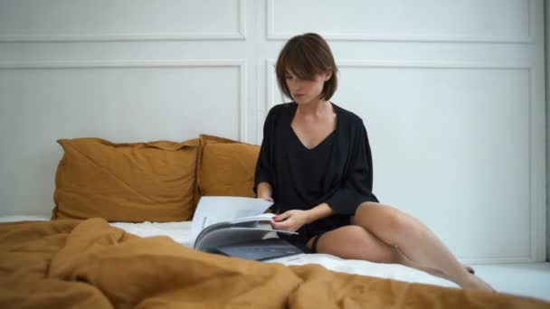 attractive woman in silk home dress reading a magazine in bed