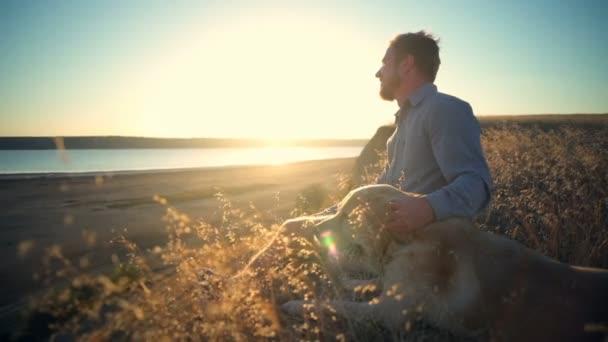 s úsměvem muž a pes sedí na okraji útesu při západu slunce