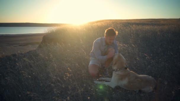 mladý muž jemně hladil starý pes, v suché trávě při západu slunce