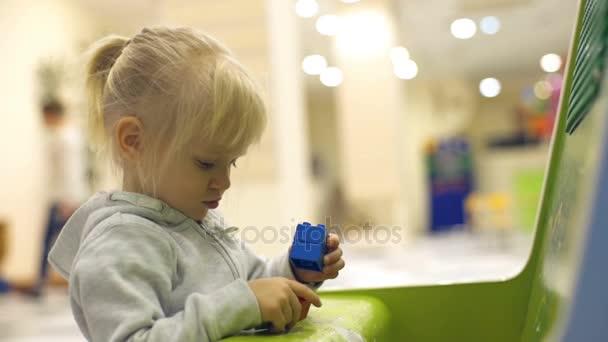 Roztomilá holčička hraje s různobarevné lego kostky pomalý pohyb