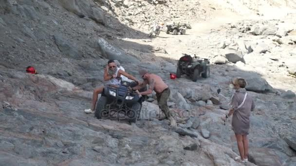 Men pushing a quad bike up the rocky hill slow motion