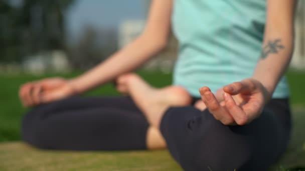 Fiatal karcsú női elhelyezés a mat lótusz póz, és meditálni zár megjelöl lassú mozgás