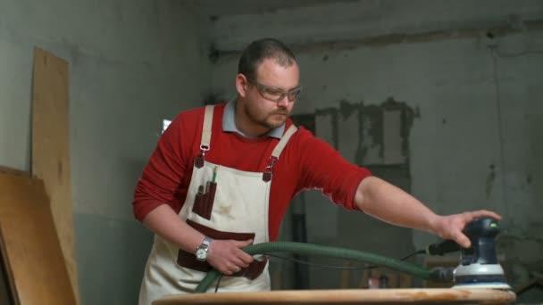 Carpenter soustředila na leštění prkno s elektrickou bruskou v dílně