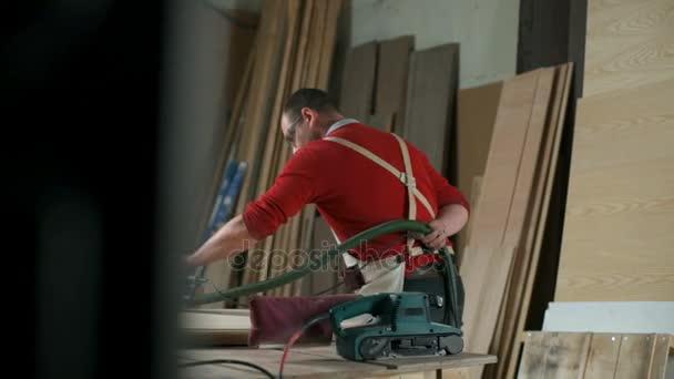 Carpenter, nosí brýle a leštění tabulku s elektrickou bruskou v dílně