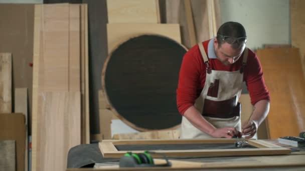 Tischler hinterlässt mit Bleistift in Zeitlupe Spuren auf Holzplanke