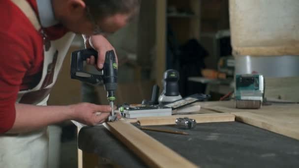 Tesař, aby otvor v dřevěné prkno s vrtačkou v dílně