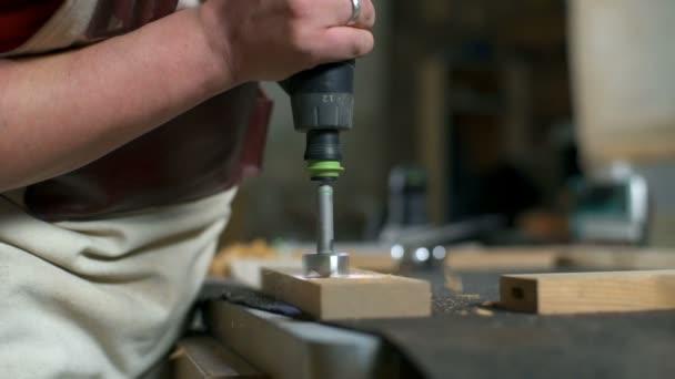 Řemeslník vrtáky otvor v dřevěné prkno s dřevorubec v dílně closeup