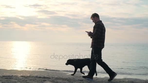 Mladý muž používat svůj smartphone při procházce se psem na moři zpomalené