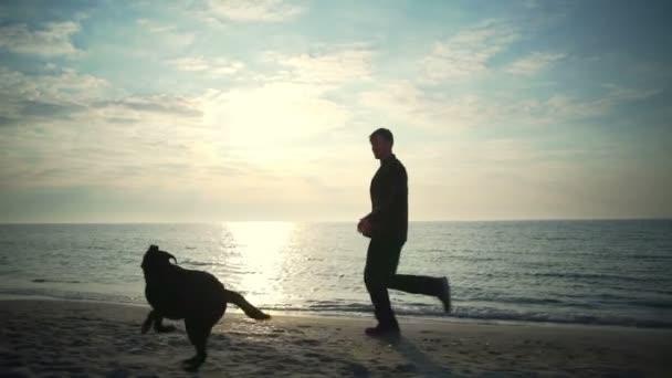 Mladý muž s jeho černého psa na zpomalené moře