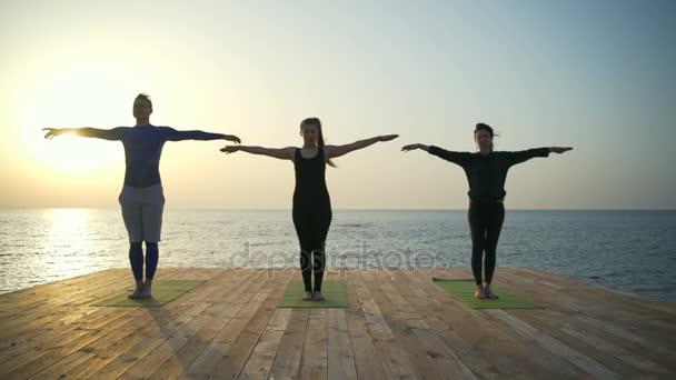 drei meditierende Personen auf der Holzterrasse in Zeitlupe