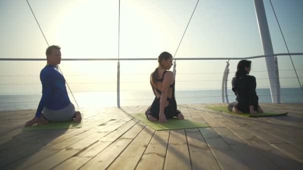 Három személy, ül a szőnyegen, csinál él közelében a bech lassú mozgás