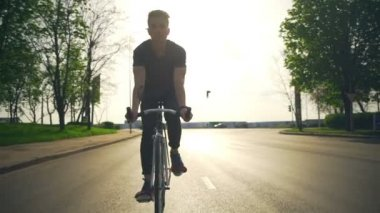 Young man rides his bicycle on the road slow motion