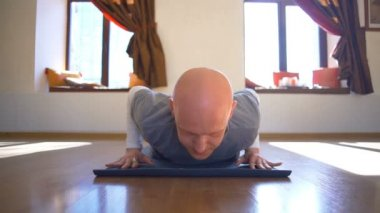 Man sits on the twine and then goes to the upward-facing dog pose slow motion