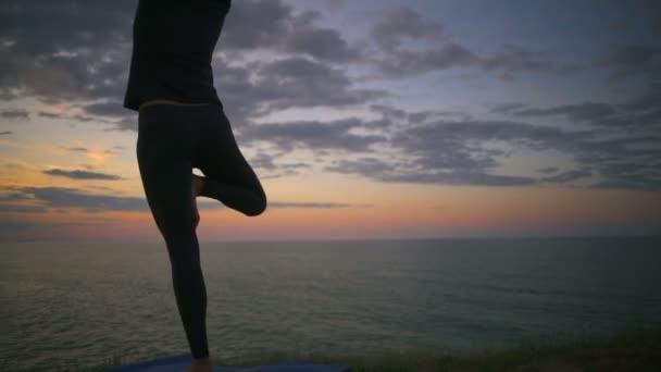 Frau meditiert, macht Yoga-Pose vrksasana bei Sonnenaufgang Zeitlupe