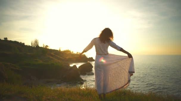 Young free beautiful healthy woman raising hand sunrise white dress slow motion