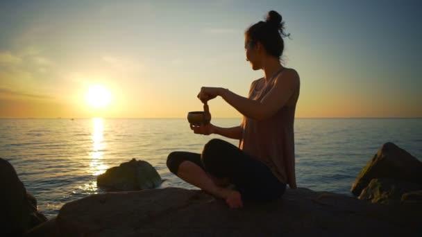 gesunde junge Mädchen meditieren tibetische Klangschalen Meeresküste Sonnenaufgang Zeitlupe