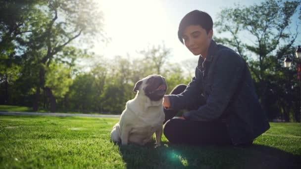 Elegantní dívka pohlazení šťastný pes plemene Mops park letní slunce zpomalený