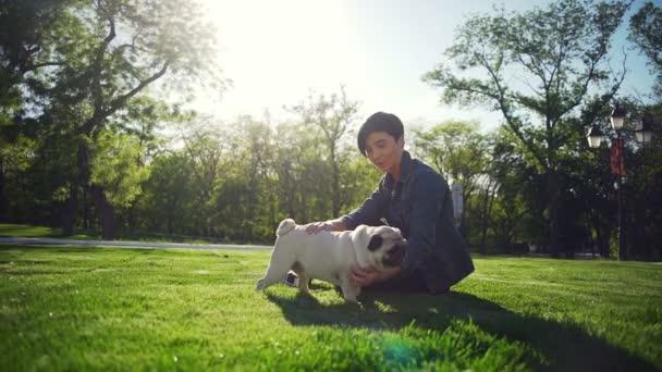 Krásná stylová holka pohlazení šťastný pes plemene Mops park letní slunce zpomalený