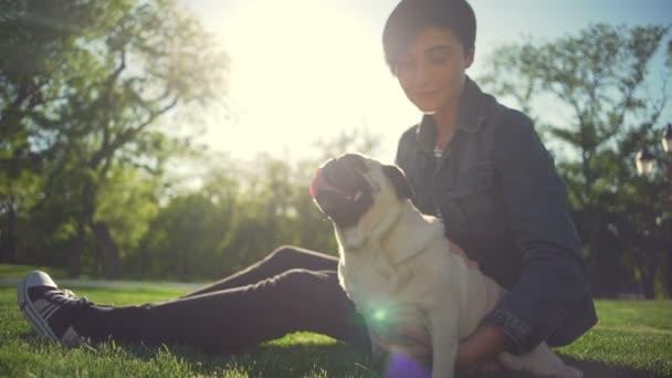 Schönes junges Mädchen sitzen und umarmen Sie Hund Mops Rasse Park Sommer Sonne Zeitlupe
