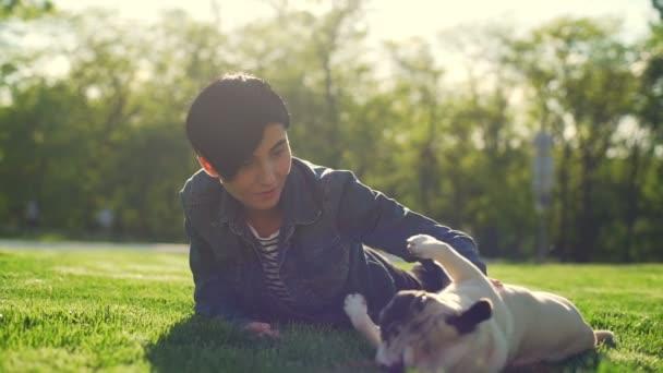Junge froh, dass Mädchen Rasen Park spielen streicheln Welpen liegt Mops Sommer-Sonne-Slow-motion