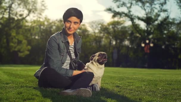 Portrét stylové ženy pohlazení šťastný pes plemene Mops park letní slunce zpomalený