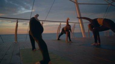 Silhouette group women trikonasana asanas yoga class sea dawn slow motion