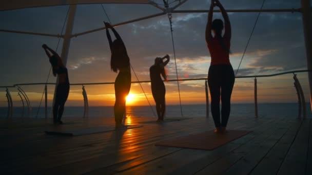 Sziluettjét csoport nők gyakorlat tadasana ászanák jóga osztály beach tenger lassú mozgás