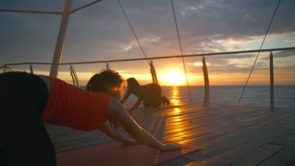 Silhouette csoport nők gyakorlat balasana ászanák jóga osztály napnyugta lassú mozgás