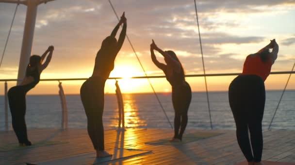 Sziluettjét csoport nők tadasana ardha uttanasana jóga osztály beach lassú mozgás