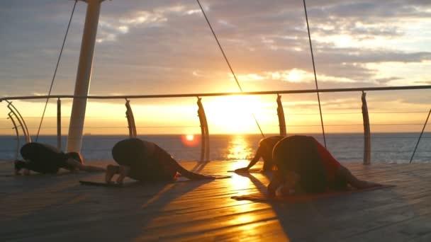 Jóga osztály fiatal nő csoport gyakorlatban asana balasana naplemente tenger lassú mozgás