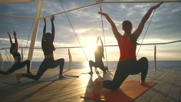 Jóga osztály csoport fiatal lány gyakorlat jóga Anjaneyasana, sunset tenger lassú mozgás