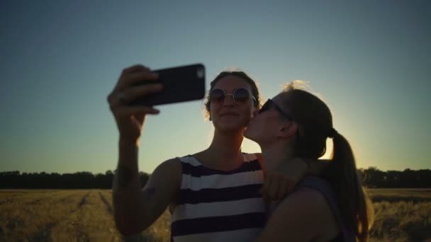 Two Smiling girlfriends sunglass make selfie kiss field sunny rapid slow motion