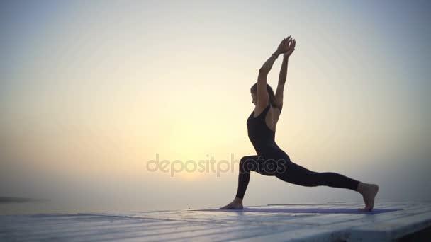 junge Frau schlank schwarz tragen Yoga niedrig Ausfallschritt Pose Sonnenaufgang Nebel schnelle Zeitlupe