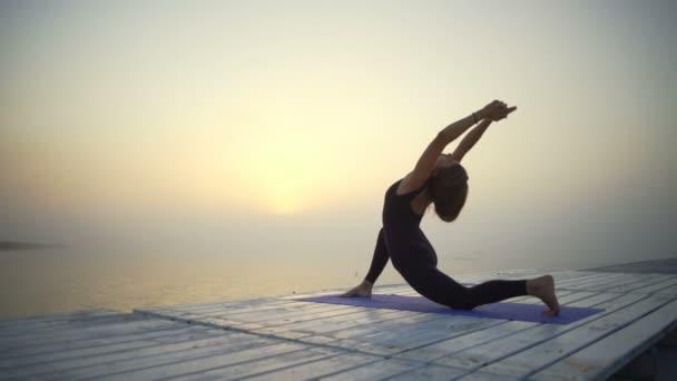 Mladá dívka slim černé oblečení dělat jógu nízké výpadu pozice sunrise mlha rychlý Zpomalený pohyb