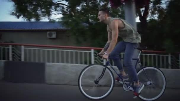 Mladý pohledný muž na kole na prázdné silnici sunrise Zpomalený pohyb rychlý