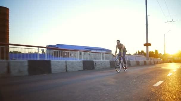 Mladá vešel muž na kole na prázdné silnici sunrise Zpomalený pohyb rychlý