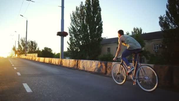 Fiatal fiú gyors lovaglás kerékpár az üres road sunrise lassított gyors alkalmas
