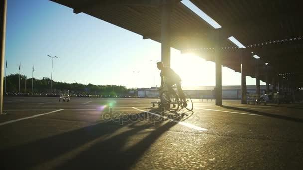 uomo che guida una bicicletta su parcheggio centro commerciale vuoto Alba rallentatore rapida