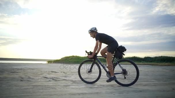 Hezký cyklista jezdit na kole helmu pískem přímořské západu slunce Zpomalený pohyb rychlý