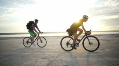 Two cyclists helmets rides sand seaside sundown slow motion rapid