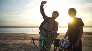 Two young cyclists make selfie on smartphone seaside dawn slow motion rapid