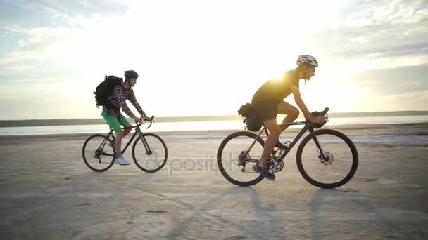 Two cyclists helmets rides sand seaside sundown slow motion rapid