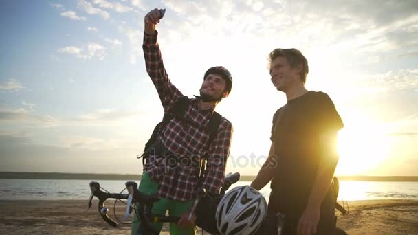 Two beautiful cyclists make selfie on smartphone seaside dawn slow motion rapid