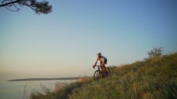 Fit mladý cyklista jezdí kolo pobřeží oceánu západu slunce helmu rychlé Zpomalený pohyb