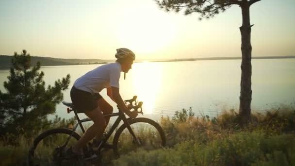 Cyklista ride bicycle pobřeží oceánu vychutnat pohled sunrise helmu rychlý pomalý pohyb